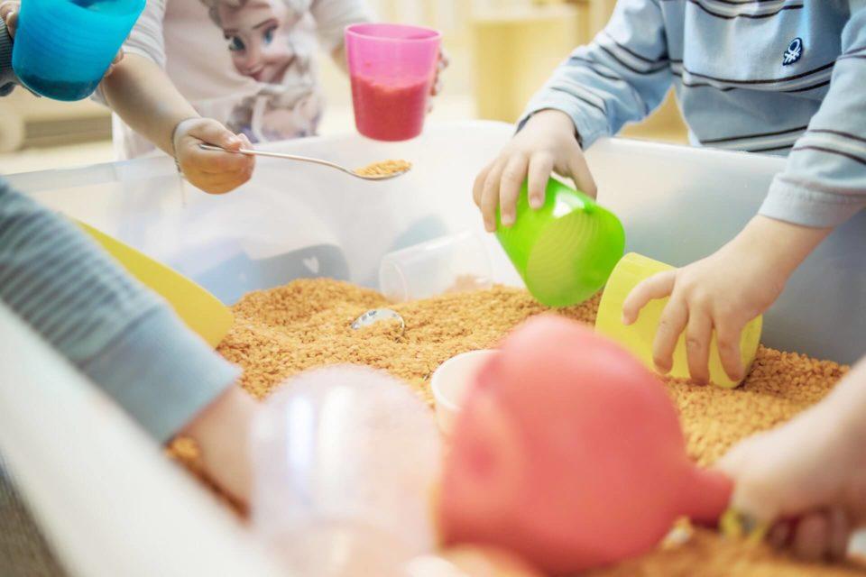 Kinder experimentieren im Zwergengarten mit Gefäßen
