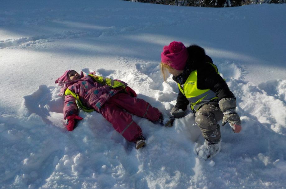Kinder des Zwergengartens spielen im Schnee