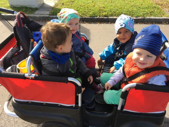 Tageskinder sind mit dem Bollerwagen unterwegs