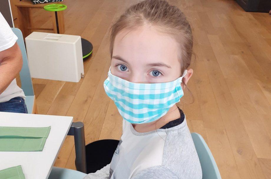 Kinder an den Mund- und Nasen-Schutz heranführen